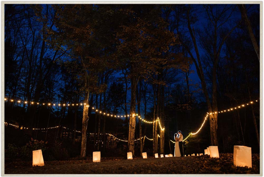 Newly weds under stringlights at the courtyard of Roxbury Barn and Estate