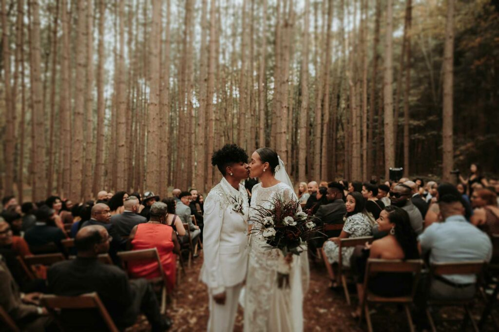 Two brides kissing in the forst at Roxbury Barn and Estate